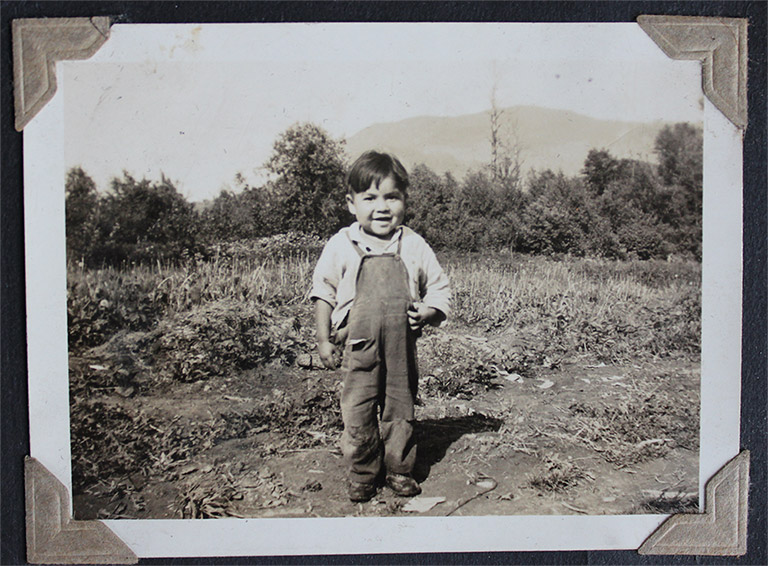 A black and white photograph of a young boy standing in a field. The boy is wearing overalls and a long-sleeved white shirt.