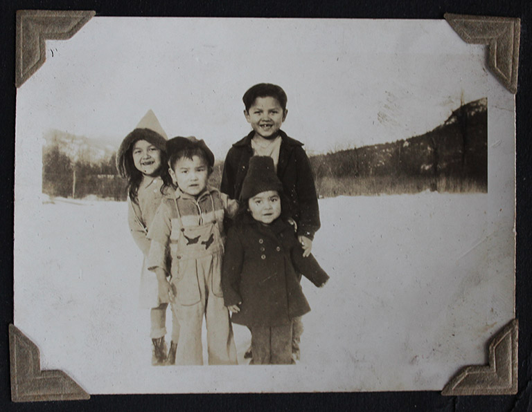 A black and white photograph of two young girls and two young boys standing in a snow-covered field. The children are all wearing winter clothes.