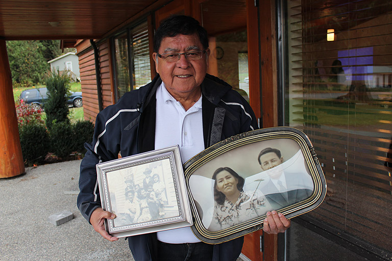 A man stands next to a building with two framed photographs in his hands.