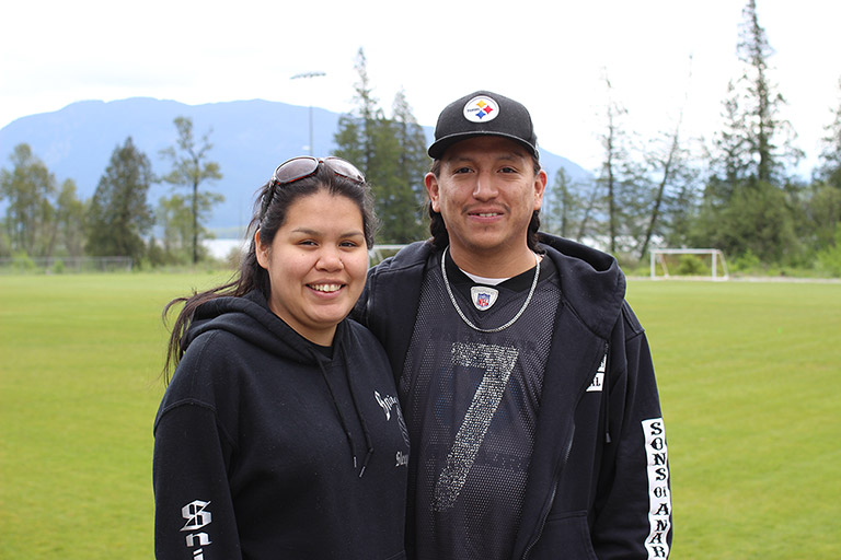 A woman and man stand next to each other in front of a soccer field. There are trees and mountains in the background.