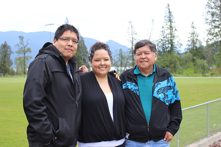 A woman stands between two men in front of a soccer field with their arms around each other. The man on the right is the father.