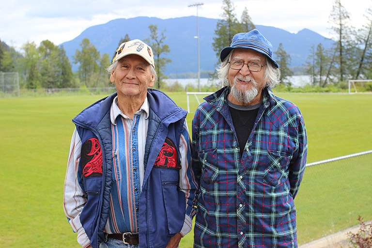 Two men stand in front of a soccer field. In the background there are trees, water, and mountains.