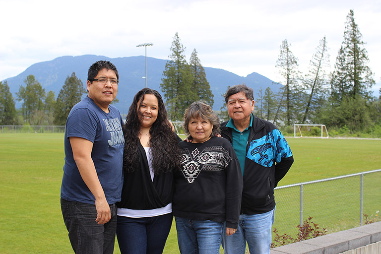 Two women stand between two men in front of a soccer field. In the background there are trees, water, and mountains.