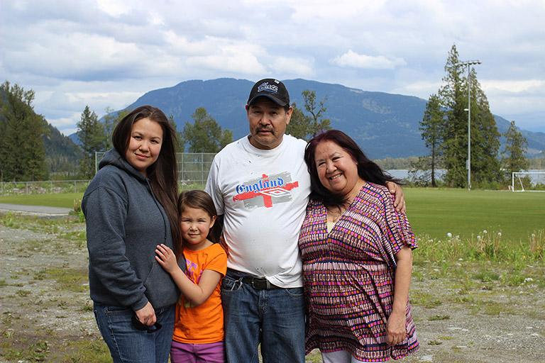 Two woman, a man, and a girl stand in front of a soccer field. In the background there are trees, water, and mountains. The young girl has her arms around the woman on the left.