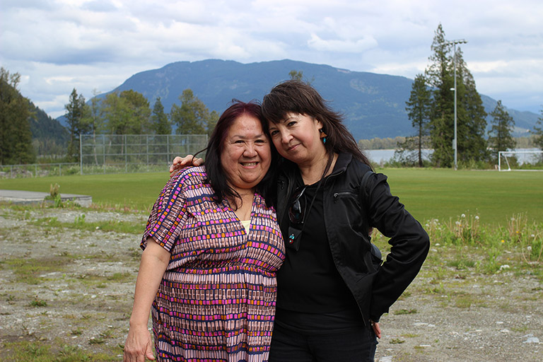 Two women stand in front of a soccer field with their arms around each other. In the background there are trees, water, and mountains.