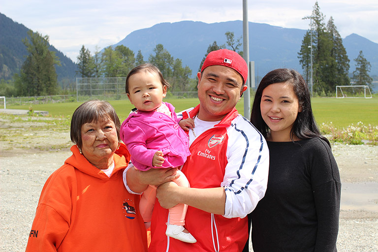 A man stands between two women in front of a soccer field. The man is holding a baby. In the background are some trees and mountains.