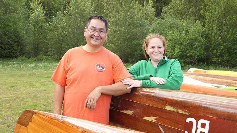 A man and woman stand outside beside a canoe, resting their arms on it. The woman is touching the man's arm with her hand.