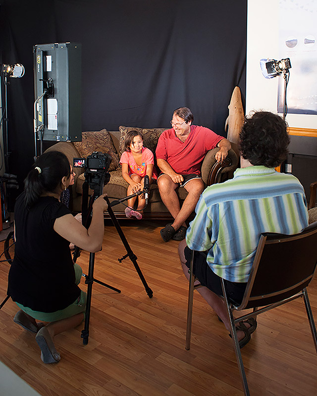 A man and a young girl sit on a couch as they are interviewed. A woman is kneeling in front of a camera on a tripod, while a male interviewer is sitting in a chair.