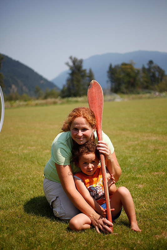 A woman kneels over a young boy in a field. The woman and boy hold a wooden paddle. In the background are some trees and mountains.
