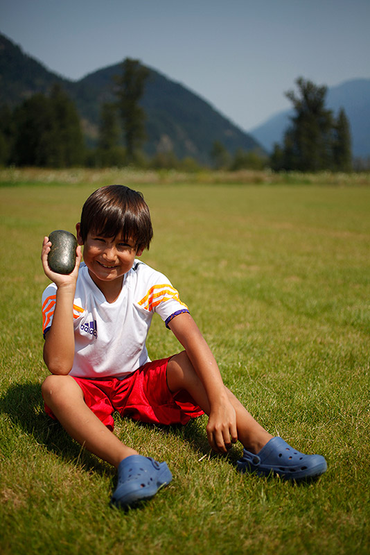 A boy sits in a field and smiles at the camera. In one of his hands he is holding up a grey object. In the background are some trees and mountains.