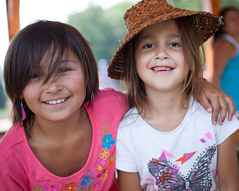 Two girls smile at the camera. The girl on the left is wearing a pink shirt and has her arm around the girl on the right. The girl on the right is wearing a white shirt and has a woven hat on her head.