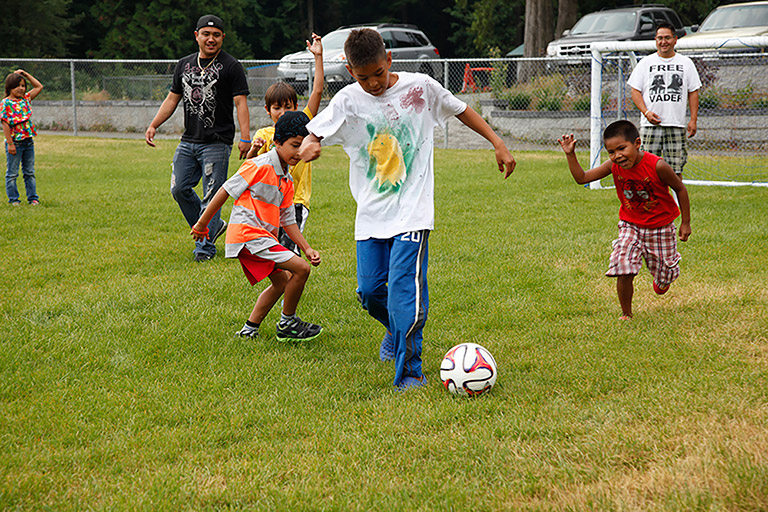 A group of men and children play soccer on a grass field. The children chase after a man dribbling with the ball.