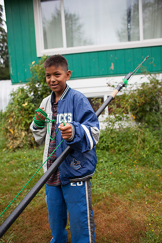 A boy stands in front of a house, holding onto a spear. The spear is taller than the boy. A green rope attached to the spear is wrapped around the boy's hand.