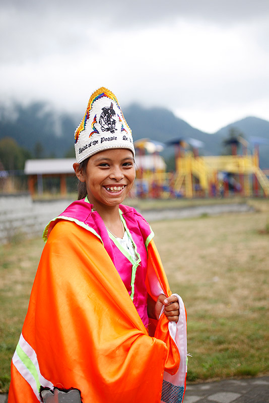 A girl wearing a fancy powwow dress smiles at the camera. The dress is bright orange, pink, and white. Her hat is white and has a black design on it.