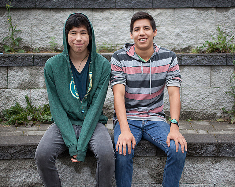 Two teenage boys sit in front of a grey stone wall. They are both smiling at the camera.