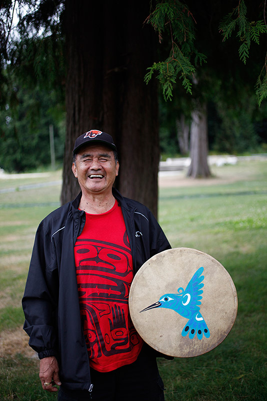 A man stands in front of a cedar tree, laughing. In his hand is a drum that has a blue hummingbird design on it.