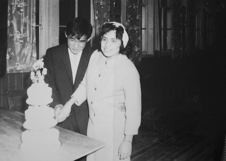 A black and white photograph of a young man and woman on their wedding day. They are cutting their wedding cake.