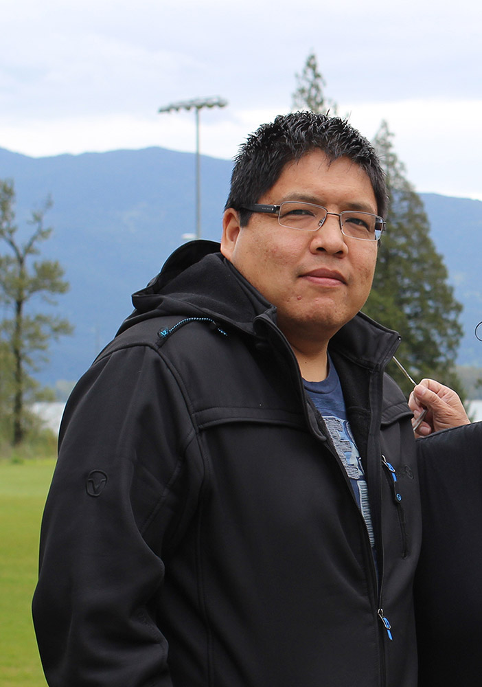 A man stands in front of a soccer field. In the background are some trees, a body of water, and mountains. He is staring into the camera.