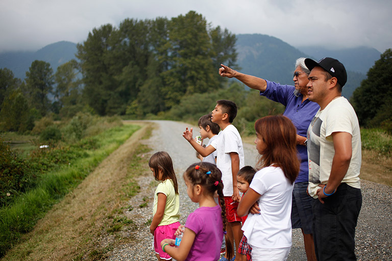 Two men and a group of children stand at the side of a road. They are staring to the side of the road at one of the men is pointing at.